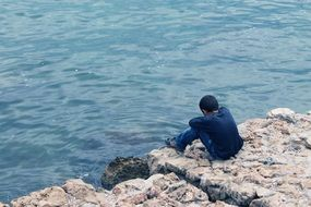 lonely guy sitting on a rock