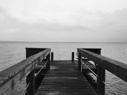 black and white photo of a wooden pier in the ocean