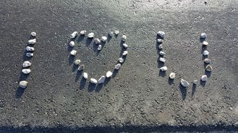I Love you, pebble lettering with Heart form on grey stone