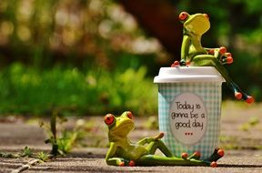 frogs near coffee as a positive day symbol