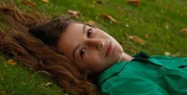girl in a green shirt lies on the lawn