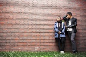 young couple near the brick wall