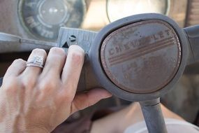 hand lies on the steering wheel of an antique car