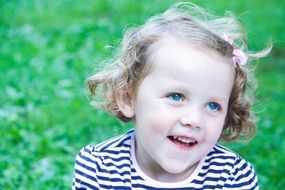 little girl with bright blue eyes in a striped T-shirt