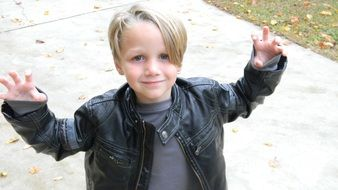 little boy in a leather jacket on the street