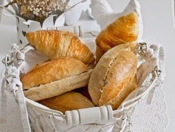 croissants and soft buns in a breakfast basket