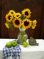 still life with a bouquet of sunflowers and apples
