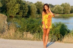 girl in a yellow dress stands on the road