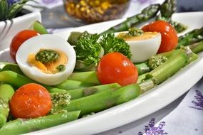 Green Asparagus wits boiled eggs and vegetables on plate