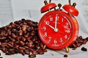 photo of a red alarm clock and coffee beans