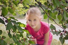 little girl stands near mulberry branches