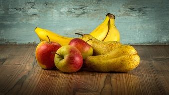 pears, apples and bananas on wooden table