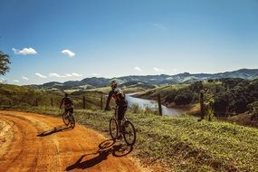 cyclists ride on a clay road