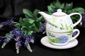 ceramic teapot with a cup near purple flowers
