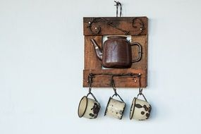 Cup shelf with decorative kettle