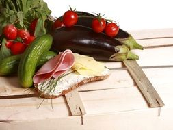 sandwich and vegetables on a wooden box