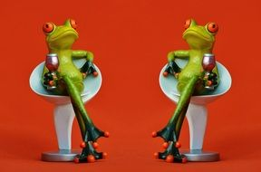 figurines of a frogs with glasses on white chairs