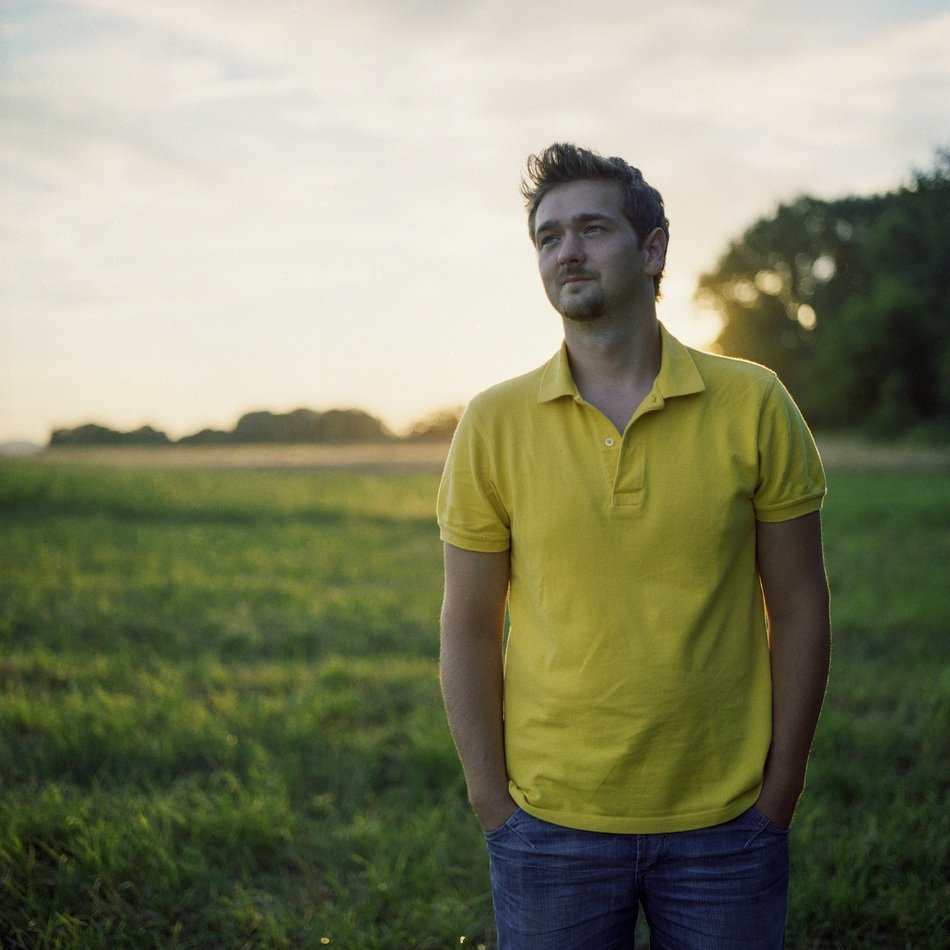 young man stands on a green field