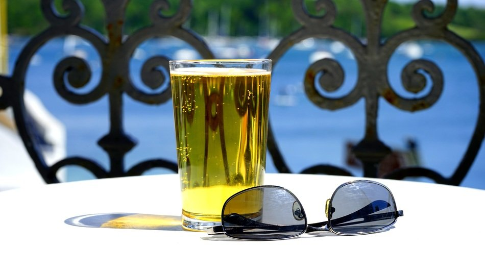 Sunglasses on the table next to a glass of beer