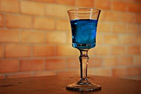 A glass of the blue alcohol drink with ice