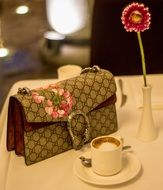 Gucci bag and cup of cappuccino