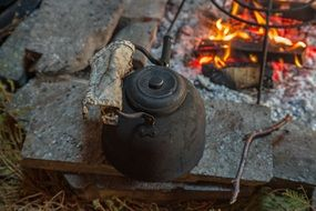 smoked teapot on stone at campfire