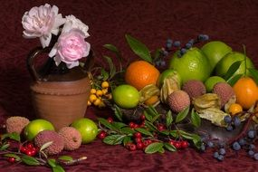 Still life with vegetables and fruits next to a pink rose