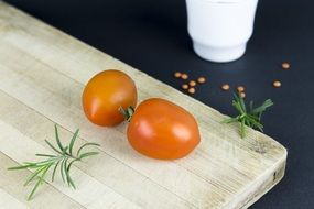 two tomatoes on a white wooden board