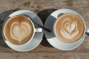 two white cups with cappuccino