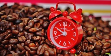 red alarm clock on coffee beans close up