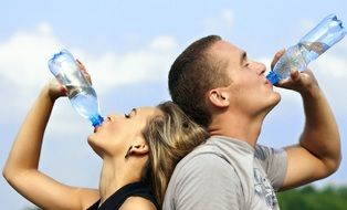 young couple drinks water from plastic bottles