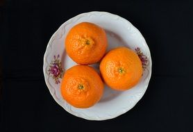 three tangerines lie on a plate