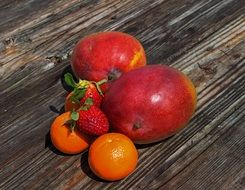 Mango, strawberries and tangerines on wooden surface