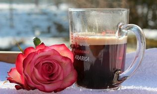 cup of coffee and a delicate rose