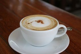 cappuccino in a white cup on a wooden table