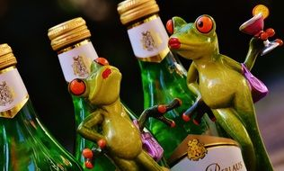 shapes of green cheerful frogs near the bottles