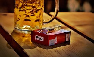 mug of beer and cigarettes on a wooden table