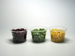 three plastic cups with multicolored beans
