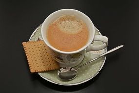 Coffee Cup with cracker on black desk