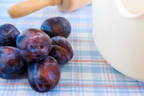 blue plums and rolling pin on the table