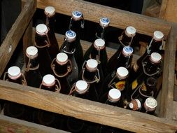 glass bottles with a drink in a wooden box