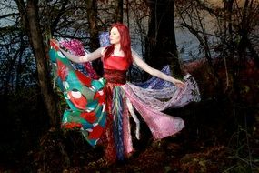 girl in a multi-colored dress in a dark forest