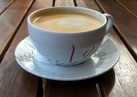 white cup with coffee on a saucer