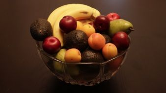 apples, apricots, bananas and avocados in a bowl