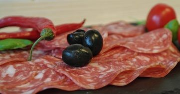 salami slices on a plate with olives