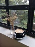 cup with aromatic coffee on the windowsill
