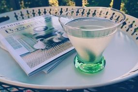 glass with martini and magazine