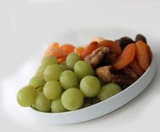 green grapes and dried fruits on a plate