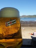 cold beer in a glass on the beach