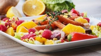 Beautiful tasty healthy salad made of the different kinds of fruits and berries